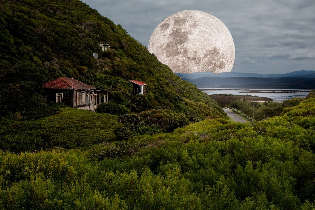 houses on a green hill with a lake and large moon in the background
